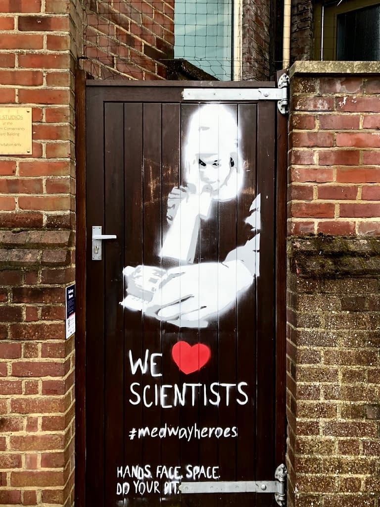 'We Heart Scientists' shows a scientist in full protective gear looking through magnifying equipment. The figure is appearing out of a door. It reads 'We Heart Scientists' Hands. Face
