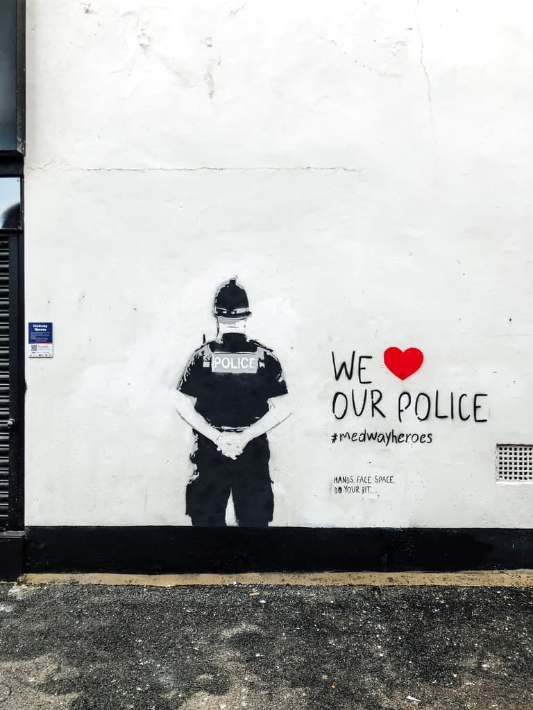 We Heart our Police shows the back of a police officer wearing a custodian helmet and with his arms behind his back. The piece is black and grey stencil art on a white wall. To the right it reads We 'red heart' our police. #medwayheroes Hands. Face. Space. Do your bit.