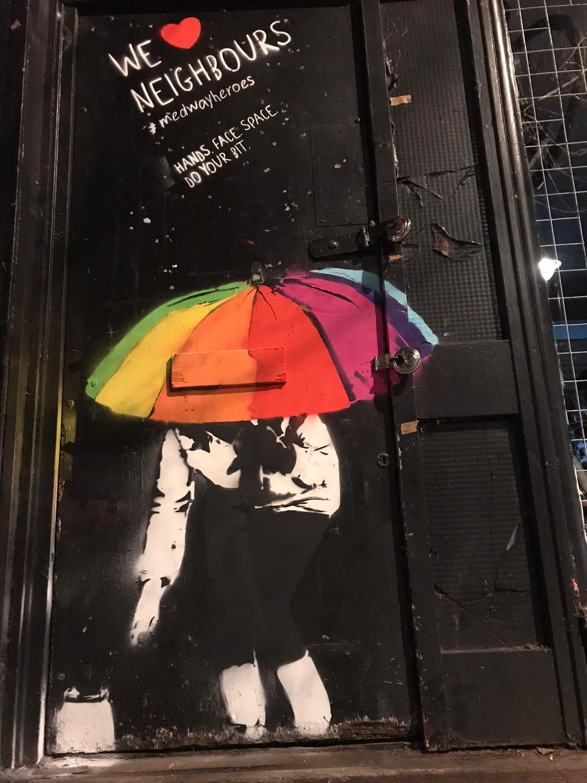 We heart neighbours is showing a woman with a rainbow umbrella on a black door dropping off a jar of food. It says We heart neighbours. #medwayheroes. Hands. Face. Space. Do your bit