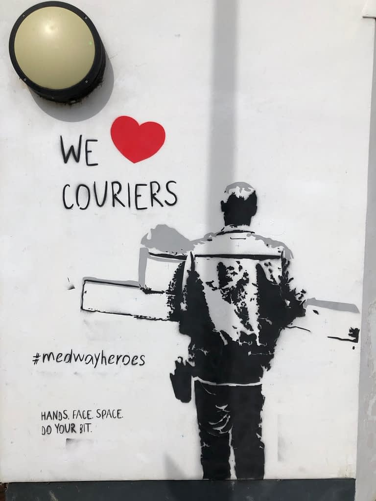 'We Heart Couriers' shows a courier in black and grey from behind delivering boxes. It says 'we heart couriers' above to the left and #medwayheroes to the left as well as 'Hands. Face. Space. Do your bit.' It's on a white wall of the Strood Community Hub