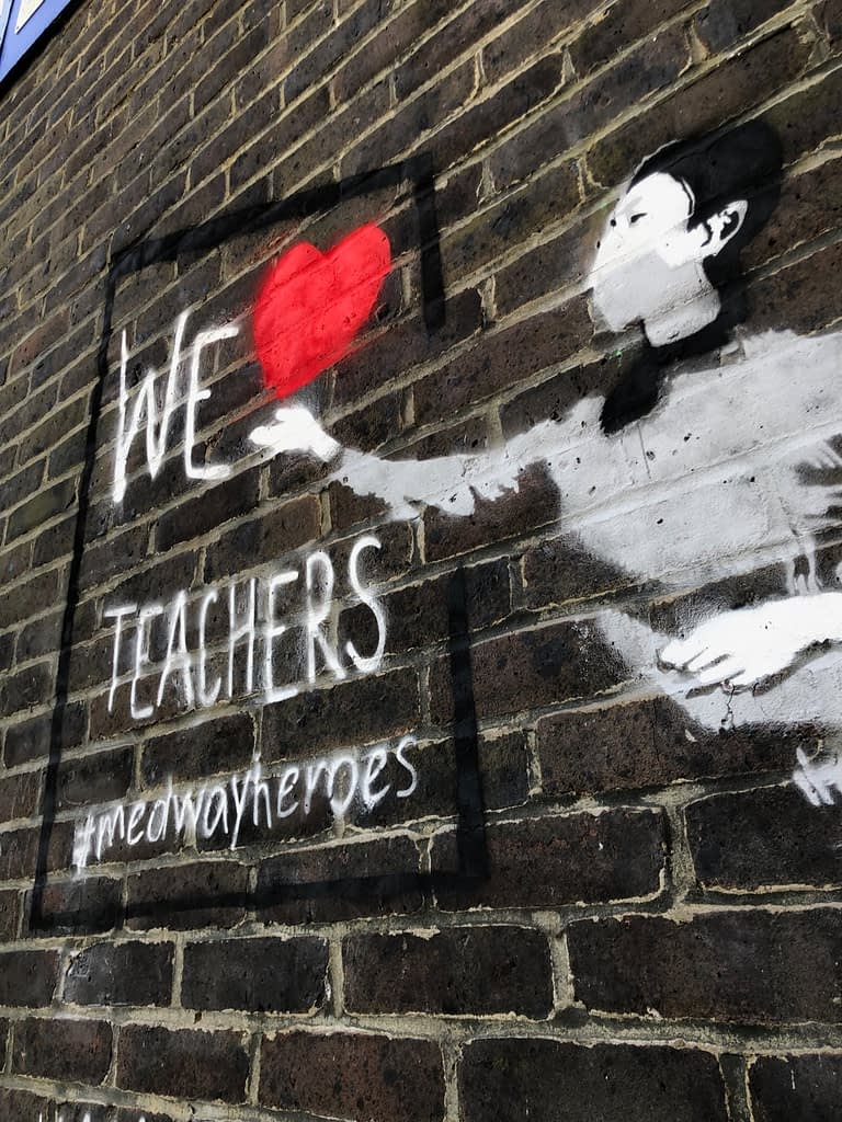 'We Heart Teachers' shows a teacher in a grey jumper and black hair pointing her right arm towards a black framed board. The red heart comes of her hand and it reads 'We heart teachers' #medway heroes.