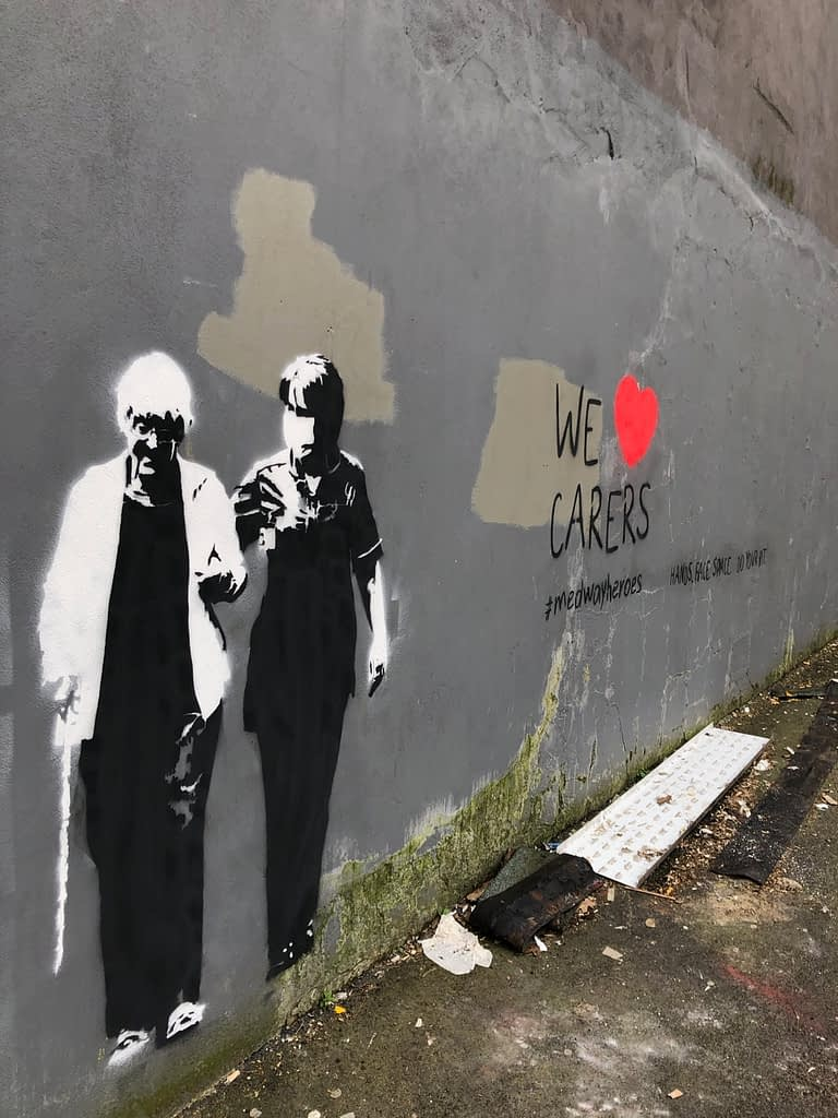 'We heart carers' shows an old lady walking with her walking stick supported by a kind masked carer. Both are in black and white. It reads 'We heart carers' to the right