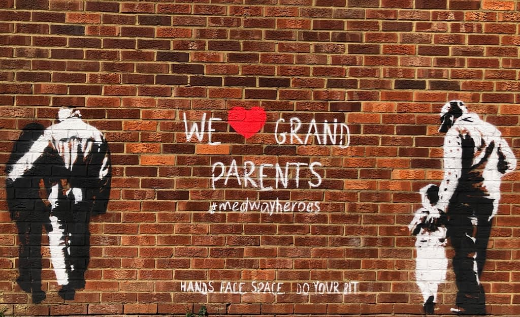 'We heart grand parents' shows a granddaughter helping her grandfather and a father looking after his daughter.  Both images are black and white on an orange brick wall. In-between the two images it reads 'We heart grand parents' #medwayheroes Hands. Face. Space. Do your bit.