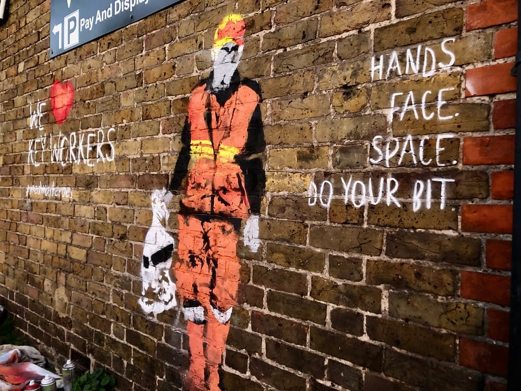 'We Heart Keyworkers' depicts a waste collector in orange, yellow, red, black and grey outfit carrying a white bin bagon a brick wall. It reads 'We heart key workers' #medwayheroes to the left and Hands. Face. Space. Do your bit. to the right