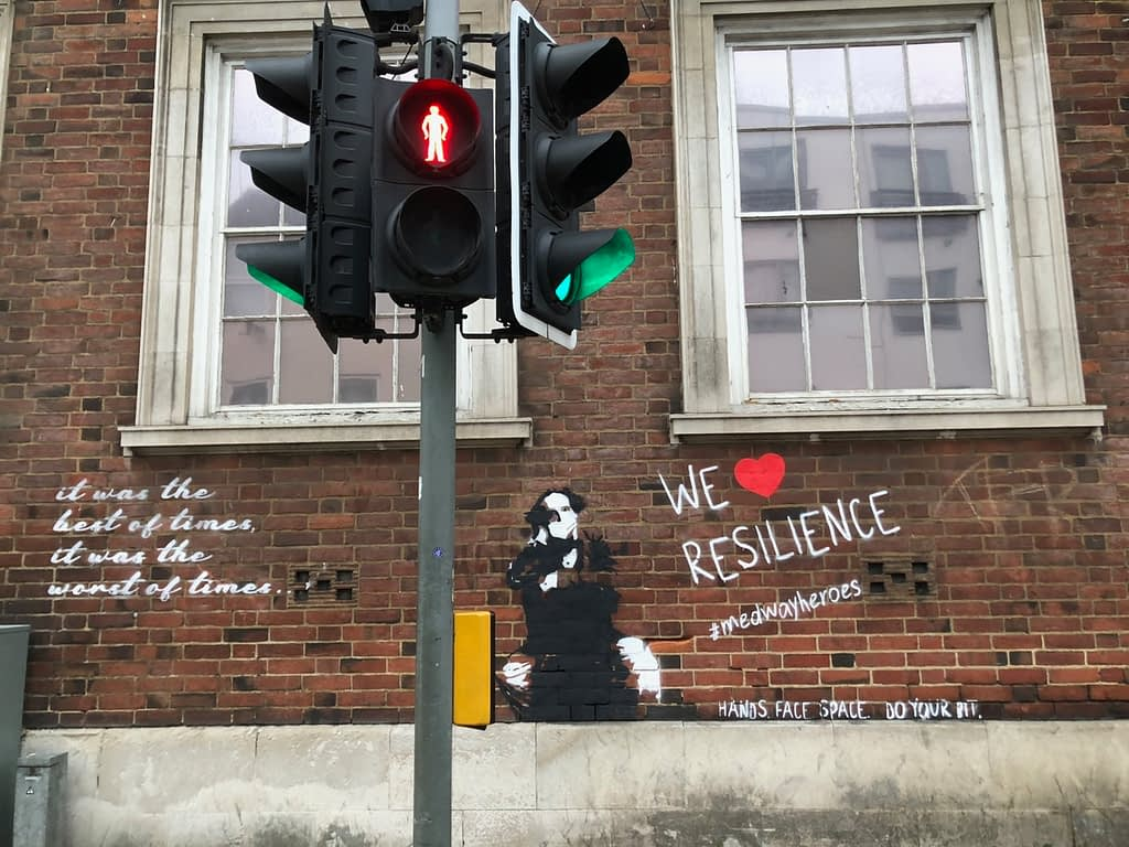 'We Heart Resilience' shows Charles Dickens in black and white wearing a mask sitting on a chair on a red brick wall. To the left it reads in cursive writing: it was the best of times, it was the worst of times. To the right it reads 'We Heart Resilience' #medwayheroes Hands. Face. Space. Do your bit.